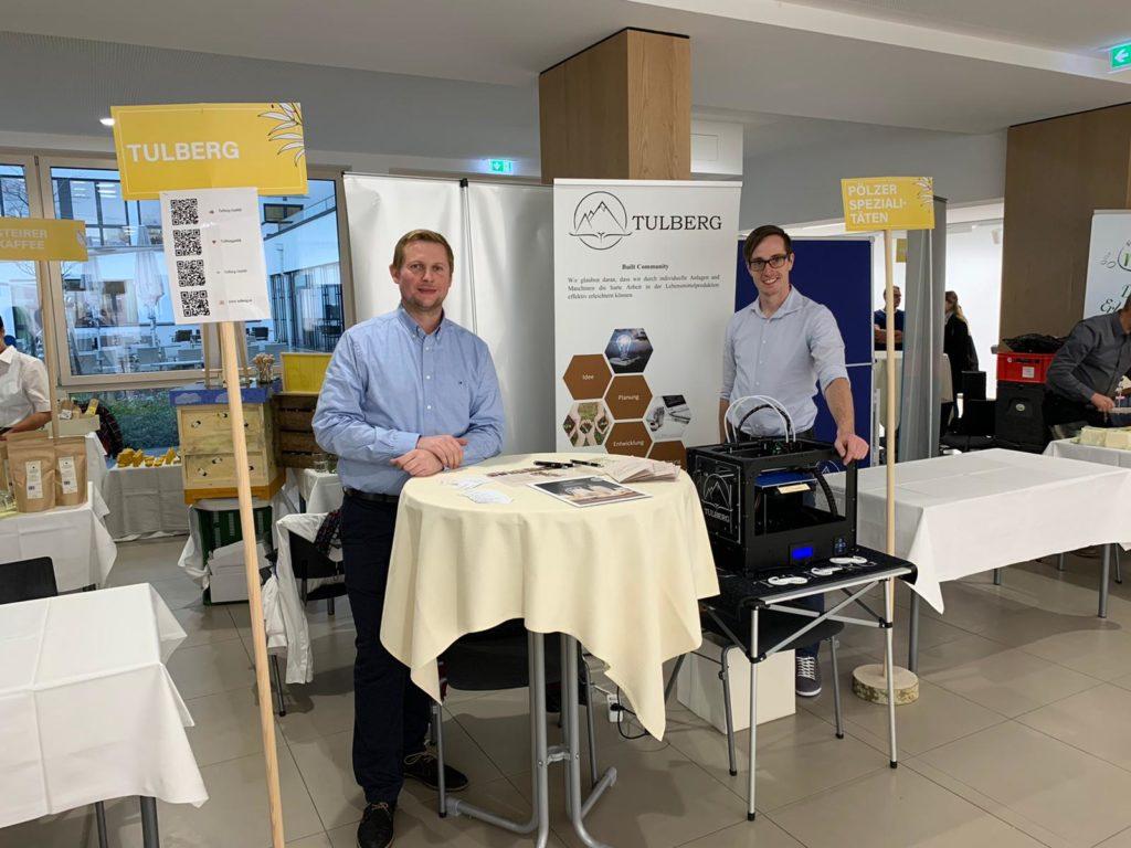 Franz Auer und Peter Gschaidbauer auf der Lebensmittelpunktmesse bei einem Stehtisch sowie einem 3D Druker.